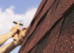 Roof repairs on background workers hands with hammer , focus on roof